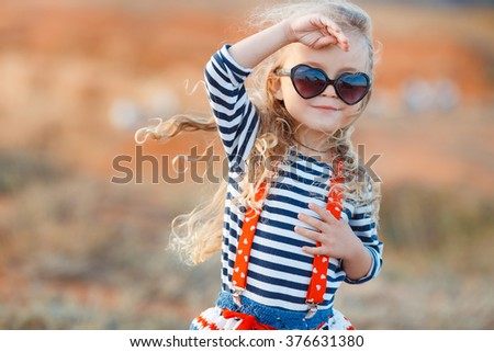 happy little girl at the seaside in the summer.Adorable little girl at beach during summer vacation. Happy baby with sunglasses by the sea or ocean - stock photo