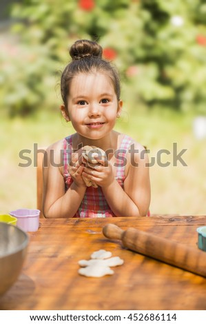 Happy little girl baking and having fun playing with dough outdoor in backyard kitchen - stock photo