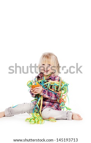 Happy little girl celebrating her birthday sitting on the floor draped in party streamers holding a birthday cake with candles, on a white background