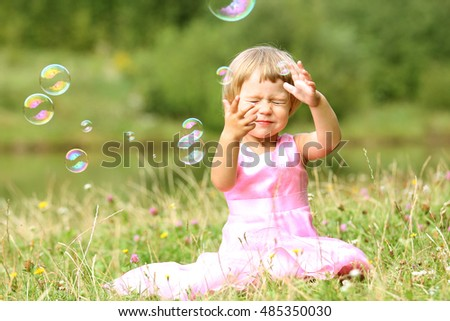 happy little girl chasing bubbles on nature in the park