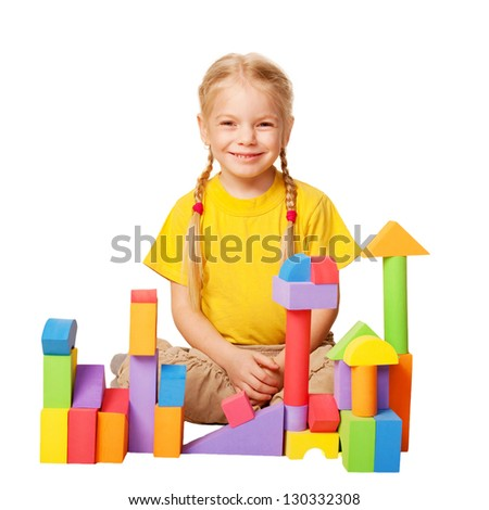 Happy little girl. Child is constructing houses from color toy blocks. Training and development of the imagination. A girl wearing yellow T-shirt. Isolated on white background - stock photo
