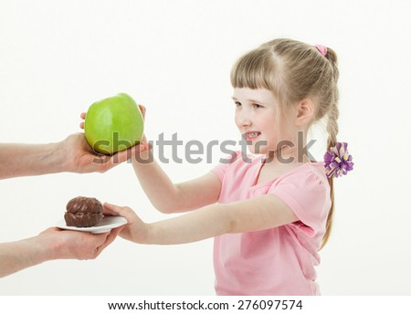 Happy little girl choosing a green apple and refusing a cake, white background - stock photo