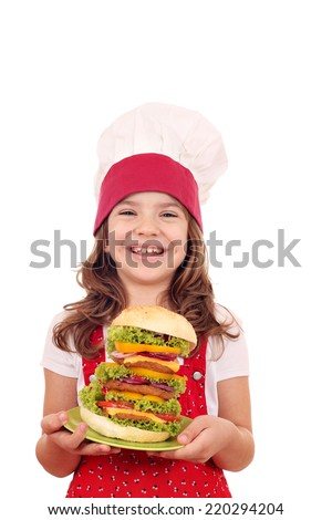 happy little girl cook holding a big hamburger  - stock photo
