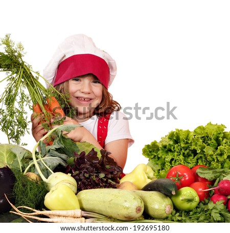 happy little girl cook with carrots and vegetables