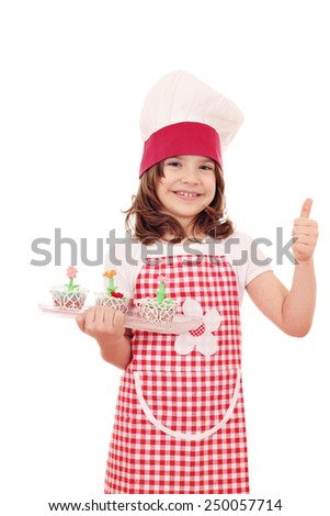 happy little girl cook with cupcakes and thumb up - stock photo