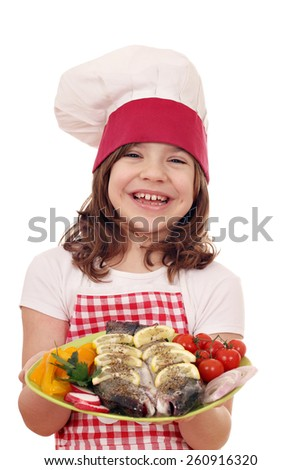 happy little girl cook with fish  - stock photo