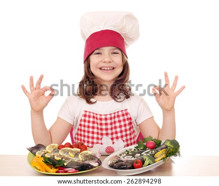 happy little girl cook with fishes and ok hand sign - stock photo