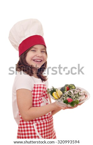 happy little girl cook with fresh trout  - stock photo