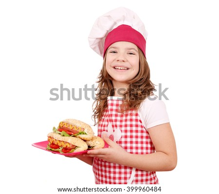 happy little girl cook with hot dogs on plate - stock photo