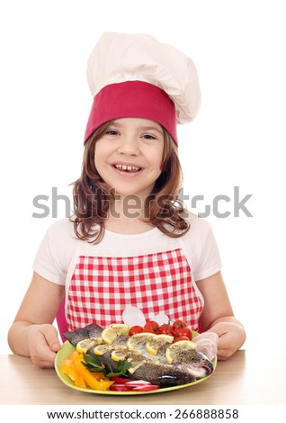 happy little girl cook with prepared fish on plate - stock photo