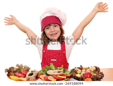 happy little girl cook with prepared salmon seafood - stock photo