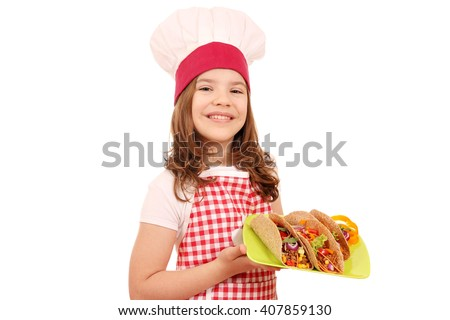 Happy little girl cook with tacos on plate - stock photo