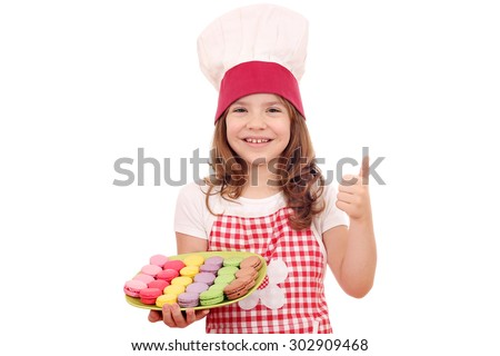 happy little girl cook with thumb up and macaroons - stock photo
