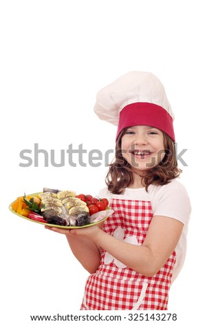 happy little girl cook with trout fish on plate - stock photo