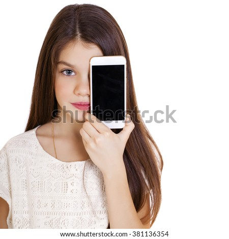 Happy little girl covers her face screen smartphone on white isolated background  - stock photo