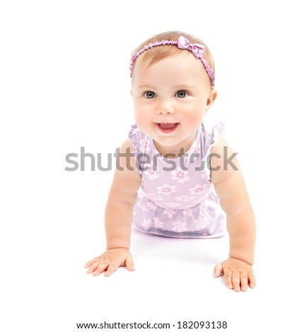 Happy little girl crawling in the studio, having fun indoors, wearing cute pink hair bow, playing isolated on white background, happiness concept - stock photo