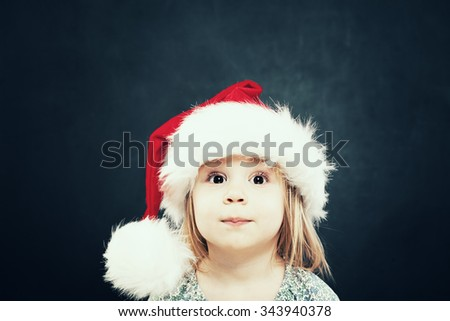 Happy Little Girl. Cute Christmas Child in Santa Hat - stock photo