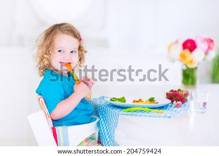 Happy little girl, cute curly toddler, eating fresh vegetables for lunch, healthy salad snack, corn, broccoli, carrots and strawberry fruit in a white dining room sitting in a high chair - stock photo