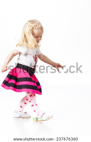 Happy little girl dancing on white background - stock photo