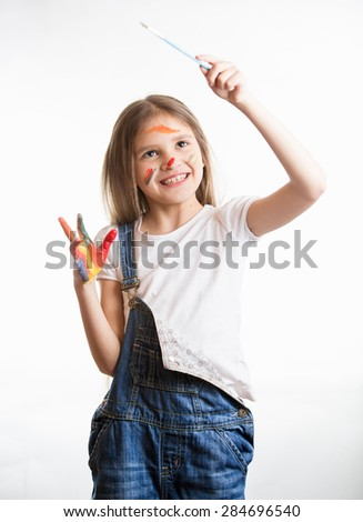 Happy little girl drawing in the air with paintbrush over white background - stock photo