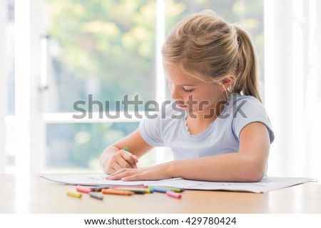 Happy little girl drawing with pencils at home. Portrait of concentrate girl coloring with crayons on copybook. Little girl painting on table. - stock photo