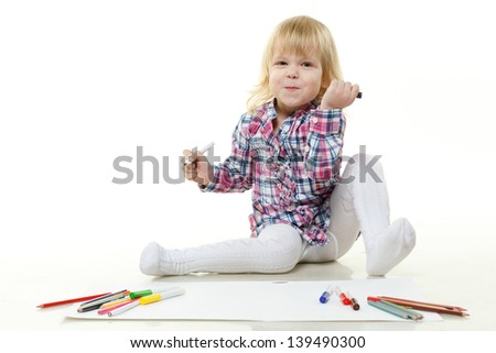 Happy little girl draws a picture on a white background.