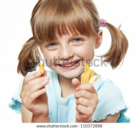 happy little girl eating a french fries - stock photo