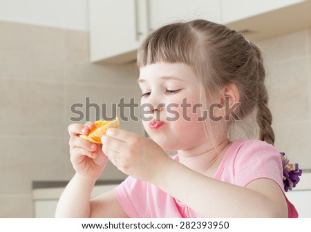 Happy little girl eating a tasty orange at home - stock photo