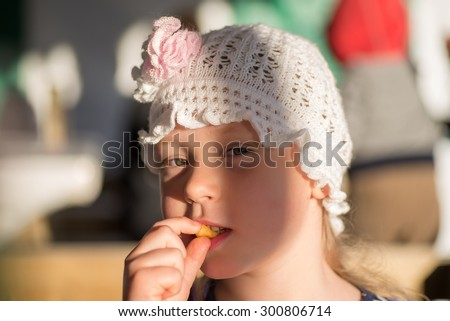 Happy little girl eating french potato. outdoor photo with natural light - stock photo