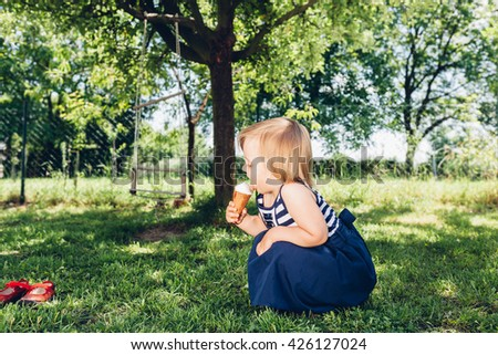 Happy little girl eating ice cream in the yard - stock photo
