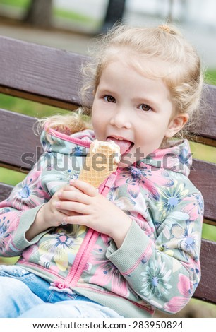 happy little girl eating ice cream outdoors