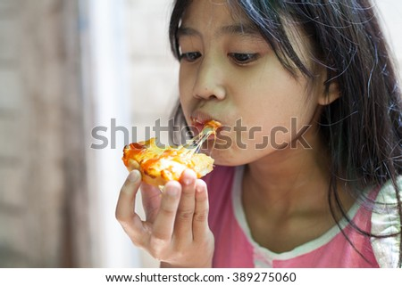 happy little girl eating pizza - stock photo