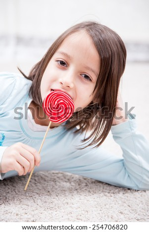 happy little girl eating sugar candy - stock photo