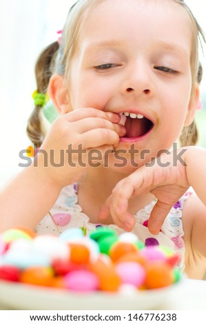 happy little girl eating sweets color candies - stock photo