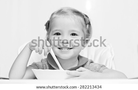 happy little girl eats with a spoon while sitting at table ( black and white ) - stock photo