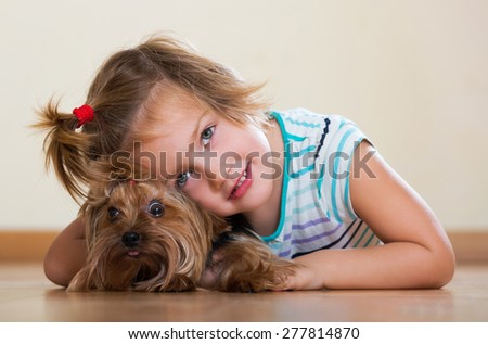 Happy little girl embraces and playing with charming Yorkie at home - stock photo