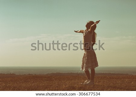 Happy little girl enjoys outdoor.Silhouette of happy little girl  Image is intentionally with grain and toned. - stock photo