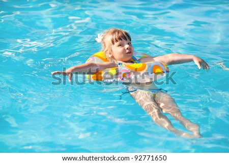 Happy little girl Floating On Water in the pool