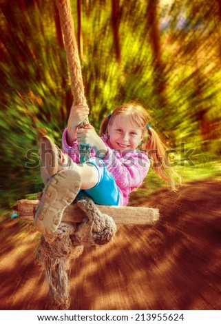 Happy little girl flying on a swing. - stock photo