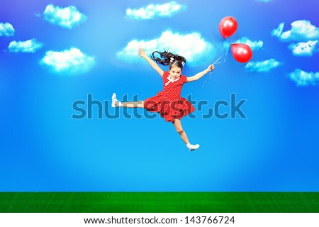 Happy little girl flying on balloons in a bright summer day. - stock photo