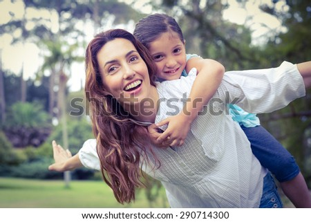 Happy little girl getting a piggy back from mother in the park on a sunny day - stock photo