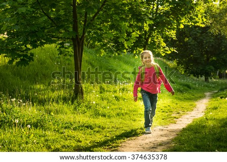 happy little girl go to school through the forest - stock photo