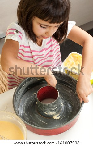 Happy little girl greasing a mold with hand to bake a cake - stock photo