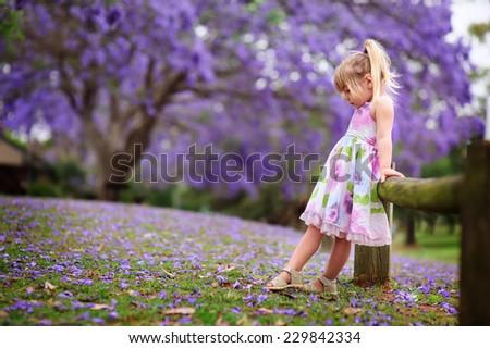 happy little girl has a fun in blossom jacaranda garden - stock photo