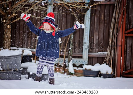 happy little girl having fun and throwing snow in winter snowy garden