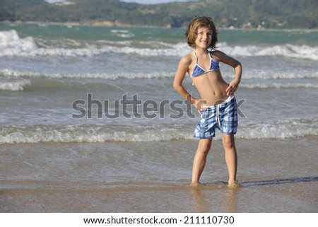 Happy little girl having fun on the beach. - stock photo