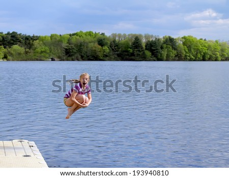 Happy little girl having fun on the lake. Jumps - stock photo