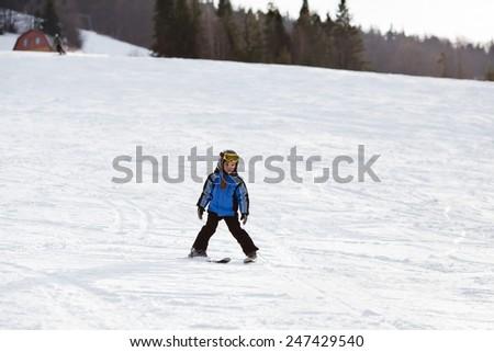 Happy little girl having fun skiing down the ski slope - stock photo