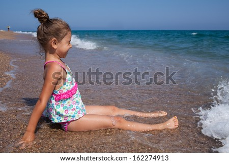 Happy little girl having fun with the sea