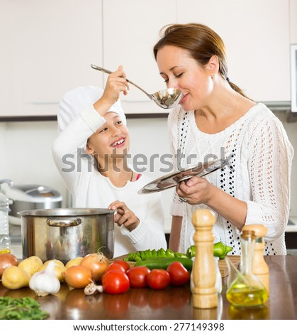 happy little girl helping mother to make soup at kitchen and smiling. Focus on woman - stock photo
